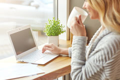 Härlig ung kvinna som arbetar med datoren på kafét som dricker kaffe och skriver på ett tangentbord Arkivbilder