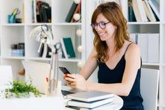 Härlig ung kvinna som arbetar med hennes hemmastadda mobiltelefon Arkivbilder