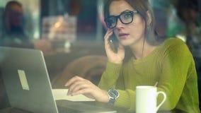 Härlig ung kvinna som arbetar och talar på en smartphone i ett kafé arkivfilmer