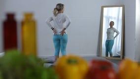Härlig ung kvinna som beundrar hennes form i spegel arkivfilmer