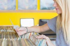 Härlig ung kvinna som bläddrar tappningrekord i vinyllagret arkivfoton
