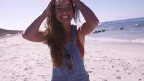 Härlig ung kvinna som blåser en kyss på stranden arkivfilmer