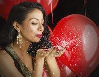 Härlig ung kvinna som blåser konfettier Royaltyfri Fotografi