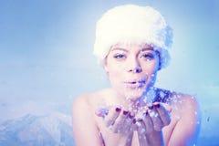 Härlig ung kvinna som blåser vintersnö Arkivbild