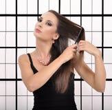 Härlig ung kvinna som borstar hennes hår på en abstrakt bakgrund Royaltyfri Foto