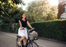 Härlig ung kvinna som cyklar längs gatan Fotografering för Bildbyråer