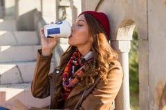 Härlig ung kvinna som dricker kaffe för att gå i en parkera royaltyfri bild