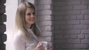 Härlig ung kvinna som dricker kaffe och att le lager videofilmer