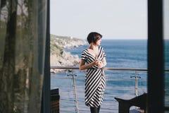 Härlig ung kvinna som dricker vin på en balkong med härlig havsikt Arkivbilder