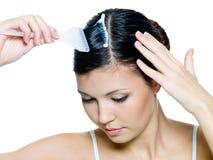 Härlig ung kvinna som färgar hår arkivbild