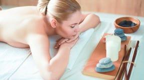 Härlig ung kvinna som får brunnsortmassagen som ligger på salong Royaltyfri Foto