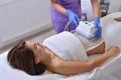 Härlig ung kvinna som får cryolipolysebehandling i skönhetsmedel royaltyfri fotografi