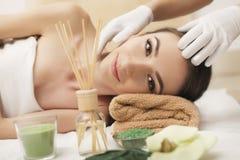 Härlig ung kvinna som får den ansikts- massagen som ligger på soffan royaltyfria bilder