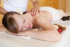 Härlig ung kvinna som får varm stenmassage royaltyfria bilder