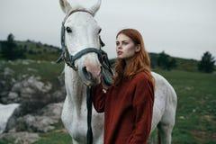 Härlig ung kvinna som går i bergen med hennes häst Royaltyfri Fotografi
