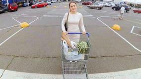 Härlig ung kvinna som går med den fulla shoppingvagnen från supermarket arkivfilmer