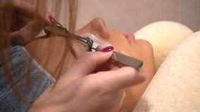 Härlig ung kvinna som gör ögonfransförlängning lager videofilmer
