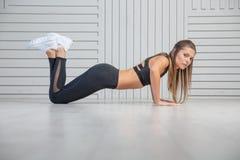 Härlig ung kvinna som gör övningar på golvet för att förstärka hennes muskler, studiostående royaltyfri foto