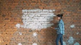 Härlig ung kvinna som gör väggmålning arkivfilmer