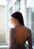 Härlig ung kvinna som håller ögonen på till och med fönstret Arkivfoto