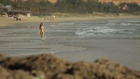 Härlig ung kvinna som har gyckel på stranden som går och att köra och att hoppa och att plaska arkivfilmer