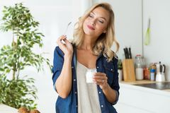 Härlig ung kvinna som hemma äter yoghurt Fotografering för Bildbyråer