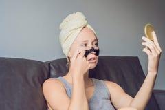 Härlig ung kvinna som hemma kopplar av med framsidamaskeringen Lycklig glad kvinna som applicerar den svarta maskeringen på frams arkivbild