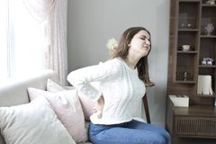 Härlig ung kvinna som hemma lider från ryggvärk royaltyfria bilder