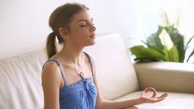 Härlig ung kvinna som hemma mediterar och att andas luft, praktiserande yoga stock video