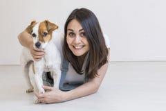 Härlig ung kvinna som hemma spelar med hennes lilla gulliga hund Livsstilstående Älska för djurbegrepp Vit bakgrund royaltyfria foton