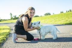 Härlig ung kvinna som joggar med hennes hund Fotografering för Bildbyråer