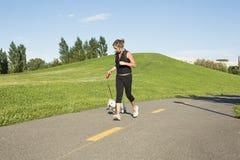 Härlig ung kvinna som joggar med hennes hund Royaltyfri Foto
