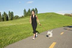 Härlig ung kvinna som joggar med hennes hund Arkivbild