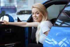 Härlig ung kvinna som köper den nya bilen på återförsäljaren arkivbilder