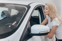 Härlig ung kvinna som köper den nya bilen på återförsäljaren royaltyfria bilder