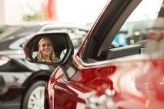 Härlig ung kvinna som köper den nya bilen på återförsäljaren royaltyfri bild