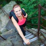 Härlig ung kvinna som klättrar en stege i naturligt/nationalpark Arkivbild