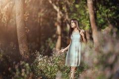 Härlig ung kvinna som kopplar av i blommamedow i skog royaltyfria foton