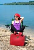 Härlig ung kvinna som kopplar av i en stol nära sjön Arkivfoton