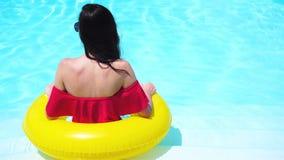 Härlig ung kvinna som kopplar av i simbassäng Tillbaka sikt av flickan i utomhus- pöl på det lyxiga hotellet stock video