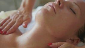 Härlig ung kvinna som kopplar av med framsidamassagen på den lyxiga brunnsortsalongen, närbild stock video