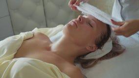 Härlig ung kvinna som kopplar av med framsidamassagen på den lyxiga brunnsortsalongen, närbild lager videofilmer