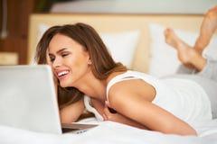 Härlig ung kvinna som kopplar av på hennes säng i den vita tillfälliga skjortan genom att använda bärbara datorn Royaltyfri Fotografi