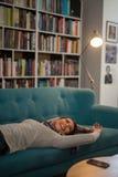 Härlig ung kvinna som lägger på en soffa i ett arkiv royaltyfri foto