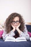 Härlig ung kvinna som läser en bok Royaltyfria Bilder