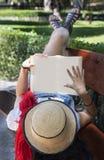 Härlig ung kvinna som läser en bok i parkera royaltyfri foto
