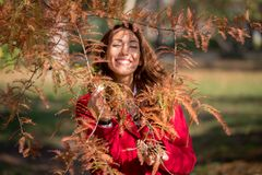 Härlig ung kvinna som ler bak ett höstträd royaltyfri foto