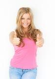 Härlig ung kvinna som ler med tummar upp Royaltyfri Bild