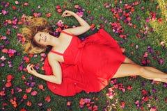 Härlig ung kvinna som ligger i blommor Fotografering för Bildbyråer
