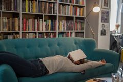 Härlig ung kvinna som ligger på en soffa i ett arkiv med en bok royaltyfri fotografi